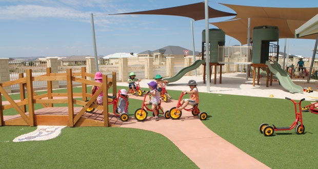 Kids ride bikes in child care playground